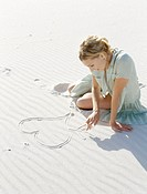 high angle view of a mid adult woman making a heart in the sand