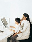 side profile of a boy working on a computer with her mother talking on a telephone