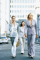 portrait of three businesswomen walking on the road