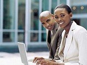 portrait of a businessman and a businesswoman sitting in front of a laptop
