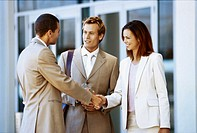 close-up of two businessmen and a businesswoman shaking hands