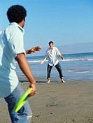two young men playing with a plastic disc on the beach