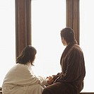 Couple in robes, looking at window