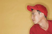 Young man wearing a red cap, against a yellow background