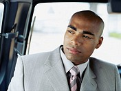 businessman sitting in a car and looking sideways