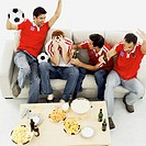 high angle view of four young men wearing soccer jerseys