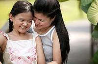Mother hugging daughter, smiling
