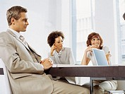 businessman and two businesswomen sitting in a conference room