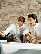 two businessmen sitting in front of a laptop and discussing work in an office