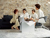 two businessmen and two businesswomen discussing work in front of a laptop