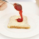 high angle view of a person´s hand spreading jam with a spoon on a slice of bread