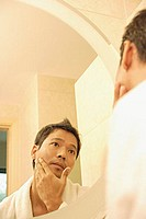 Young man touching his face, looking in mirror