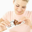 close-up of a young woman taking chocolate out of the wrapper