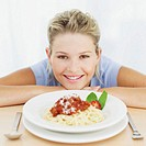 portrait of a young woman with a plate of spaghetti bolognaise