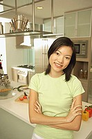 Young woman leaning on kitchen counter, arms crossed, looking at camera