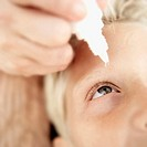 close-up of a person´s hand putting eye drops into a boy´s eye