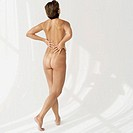 rear view of a naked mid adult woman standing with her hands on her back