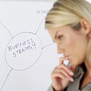 close-up of a businesswoman standing in front of a whiteboard