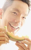 Man holding melon slice, smiling