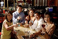 Group of people raising wine glasses, looking at camera