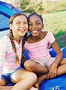 Portrait of two girls outside a tent, smiling