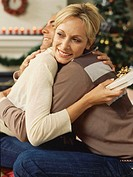 Side profile of a mid adult woman holding a gift and hugging a mid adult man