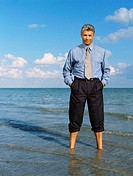 Portrait of a mature man standing on the beach with his hands in his pocket
