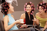 Young women at beauty salon, drinking tea and talking