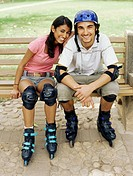 Portrait of a young couple sitting on a bench wearing inline skates