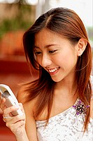 Young woman holding mobile phone, smiling