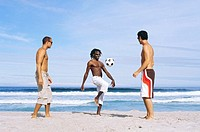 Three young men playing football on the beach