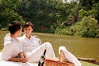 Couple sitting by a lake, with picnic basket, looking at each other