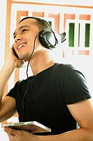 Young man listening to music, wearing headphones, looking away