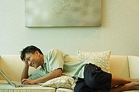 Man lying on sofa, using laptop