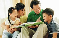 Grandparents with two grandchildren, book open between them