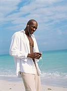 Young man walking on the beach and listening to an mp3 player