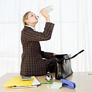 Businesswoman sitting on her office table and drinking vodka from the bottle