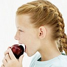 Young girl (10-11) eating a plum