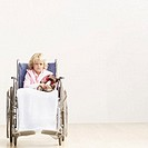 Portrait of a young girl (8-10) sitting in a wheelchair holding her teddy bear