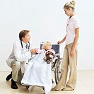 Male doctor pushing a young girl (8-10) in a wheelchair with a young woman beside her