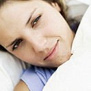 Close-up of a sick young woman lying in bed
