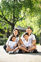 Family looking at camera, sitting on ground