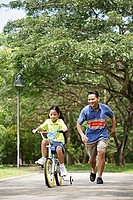 Girl cycling away, father running behind her
