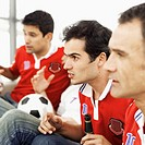 Side profile of four young men watching television wearing soccer jerseys