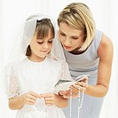 Close-up of a girl listening to her mother before her first holy communion