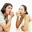 Portrait of a young couple eating red and green apples