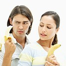 Portrait of a young couple holding bananas