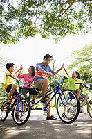Family, on bicycles, giving each other high fives