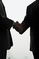 Businessmen shaking hands, silhouette