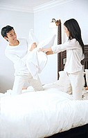 Couple on bed, having a pillow fight